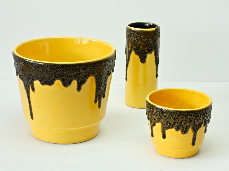 A tall, cylindrical, beautiful and bright vivid yellow vase attributed to Fohr Pottery although similar vases were made by ES Keramik, circa 1970. The bright yellow looks wonderful against the textured black fat lava drip glaze.   A wonderfully