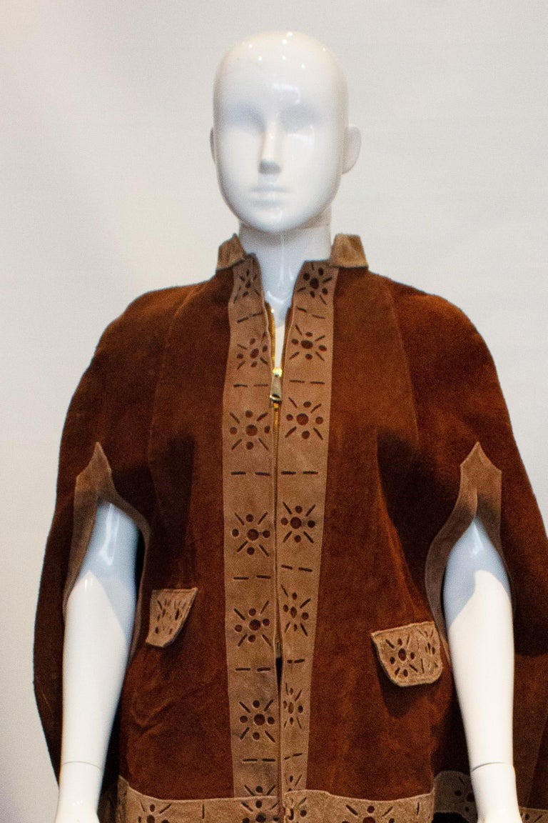 A fun vintage cape from the 1970s in brown suede.  The cape has a front zip fastening, with two arm slits and two flap pockets at the front. It is edged in a lighter brown suede. Measurements : Shoudl to shoulder 18'', length 27''