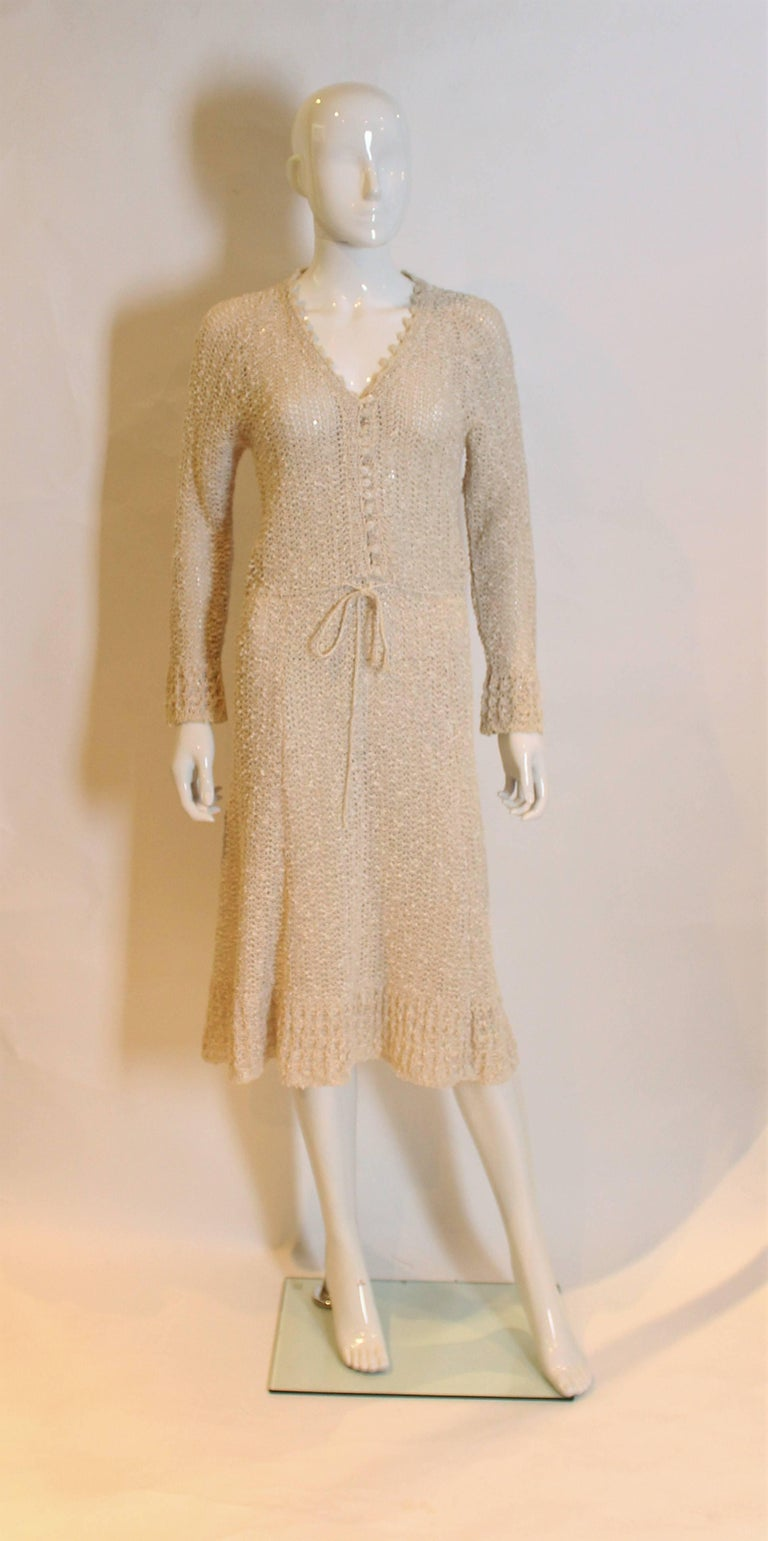 this is a lovey handloomed Irish linen crochet dress.It has a v neckline, long sleeves, and buttons to waist.The waist has drawstring and a flared skirt.