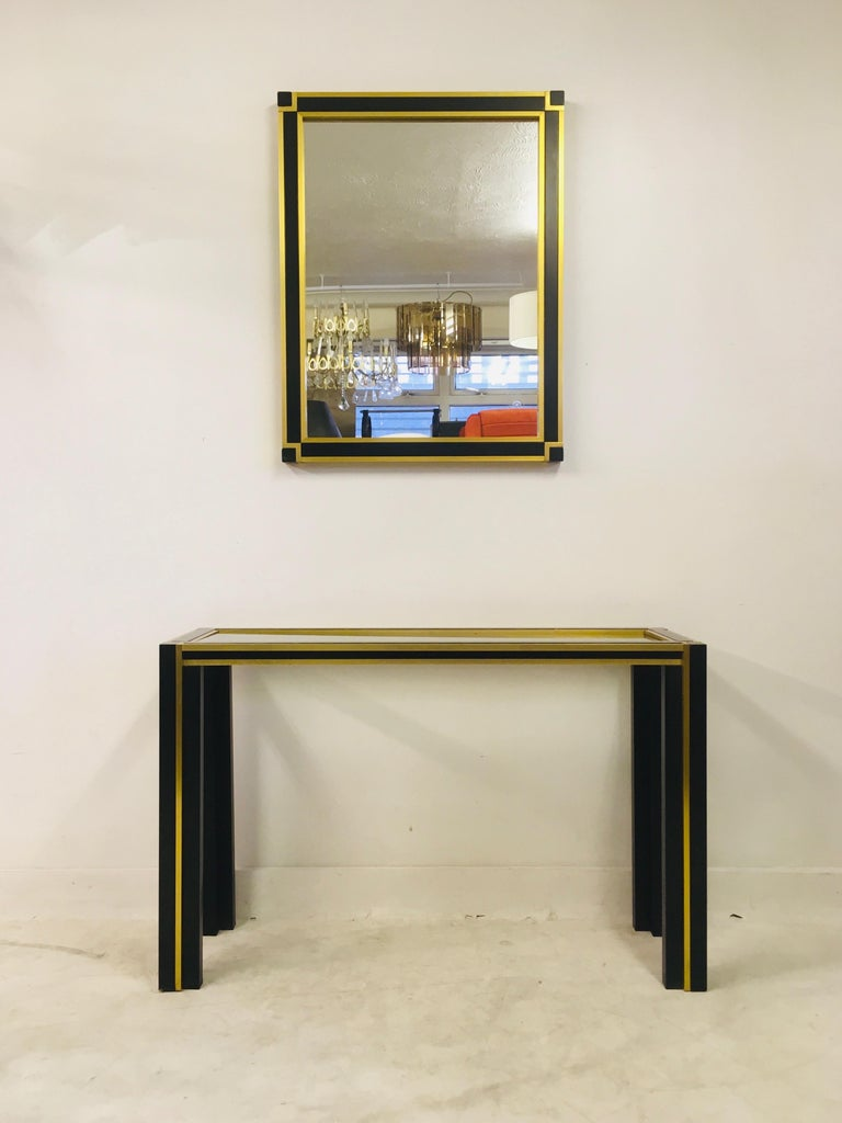 Vintage console table and mirror  Black metal frame  Brass banding  Mirror measures 90 x 70cm  Italy, 1970s.