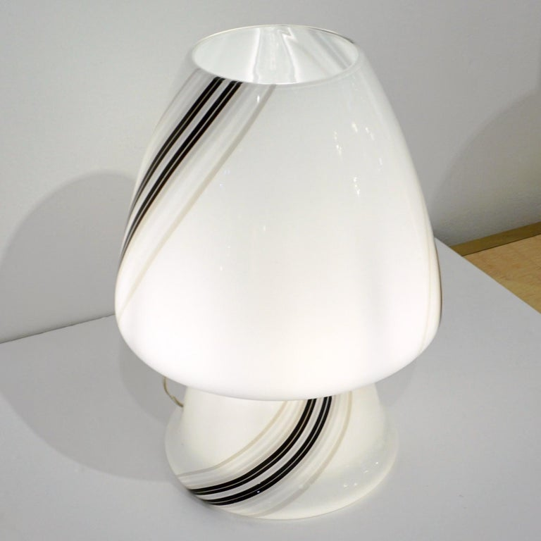 A delightful mid-20th century modern Italian design table lamp, attributed to Vistosi, of organic conical mushroom shape, skillfully blown as a whole single piece in white Murano glass artistically decorated with elegant swirling black and gray