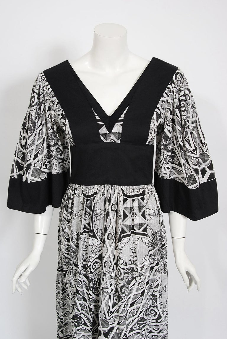 Gorgeous early-1970's Thea Porter designer couture dress fashioned in magical black and white kaleidoscope floral cotton print. I love the dramatic bell-sleeves and bold block coloring. The silhouette is a flattering nipped-waist full length design.