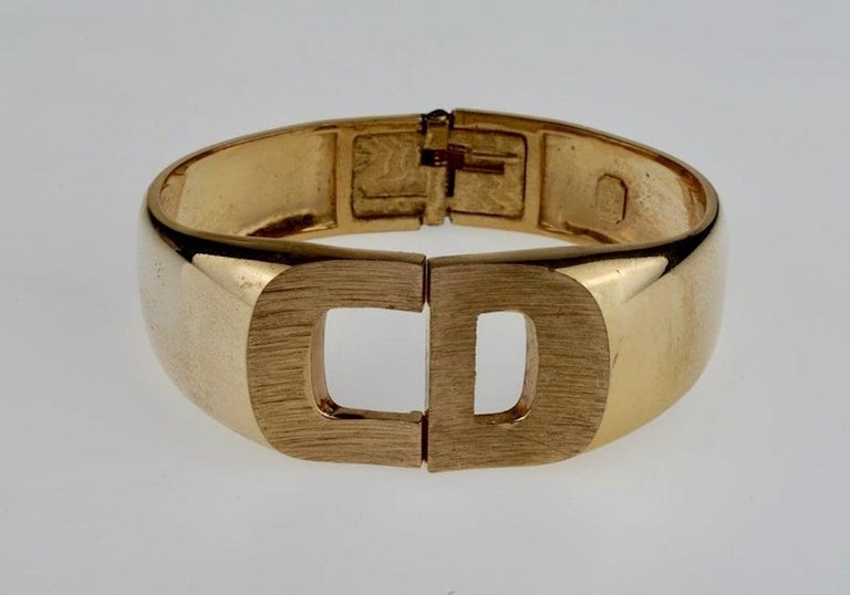 Vintage 1972 CHRISTIAN DIOR Logo CD Clamper Bracelet Cuff  Measurements: Height: 1 1/8 inches  Features: - 100% Authentic CHRISTIAN DIOR. - Textured CD logo at the centre. - Rigid clamper bracelet cuff. - Signed 1972 CHRISTIAN DIOR Germany. -