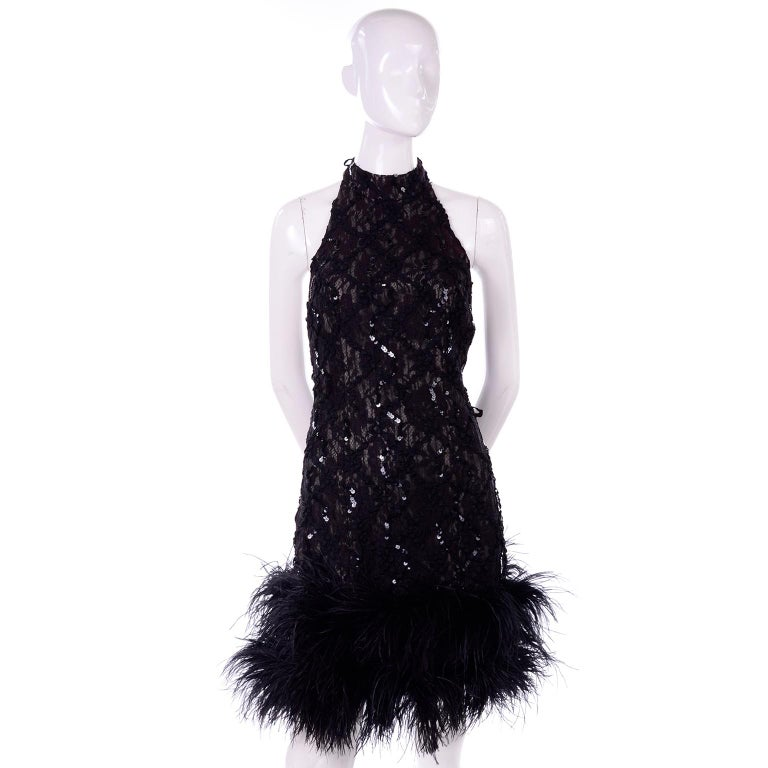 This is a stunning vintage black lace halter dress, covered with sequins and trimmed with black ostrich feathers. The dress has a halter neck and there is a small amount of burgundy in the lace.  Perfect for cocktail parties, special occasions and