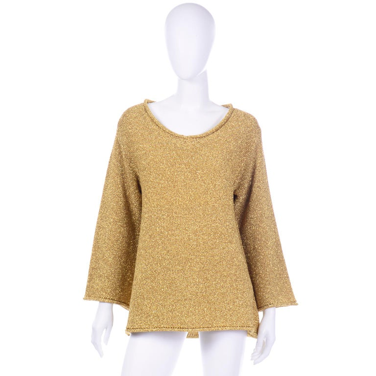 This is such a stunning vintage 1980's gold metallic knit pullover sweater from Claude Montana. This beautiful top has a slightly scooped round neckline with an open knit and rolled edge that is also found around the cuffs of the sleeves and hem.