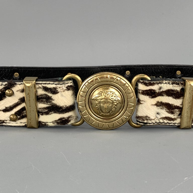 Vintage GIANNI VERSACE belt features a brown and cream zebra print ponyhair leather strap with gold tone Medusa head studs and round Medusa head buckle. Made in Italy.  Very Good Pre-Owned Condition. Marked: 80/32  Length: 32 in. Width: 1.5