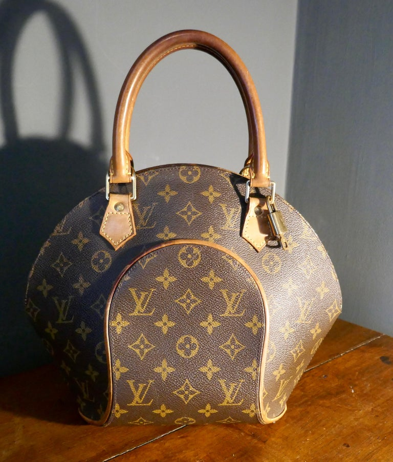 Vintage 1990s Louis Vuitton Ellispe MM Hand Bag  The Ellipse MM is a stiff bag featuring rolled vachetta handles, made in Monogram canvas with vachetta trim, a double top zip closure, an interior flat pocket, and a D-ring, monogram studs, original