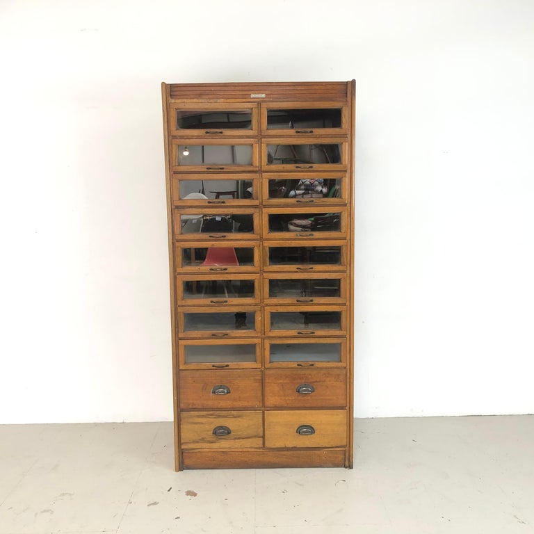 Really lovely vintage 20-drawer haberdashery shop cabinet from the 1920s with brass handles and panelled sides. Made by J C King.  In good vintage condition. Some scuffs here and there, commensurate with age, and signs of historical woodworm which