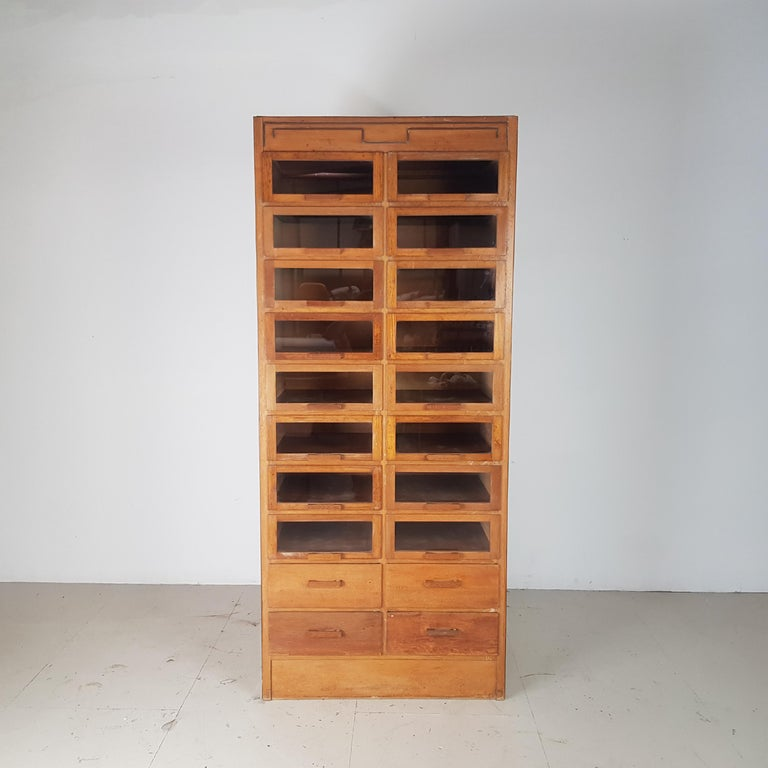 Really lovely vintage 20-drawer haberdashery shop cabinet from the 1940s-1950s with wooden handles. Made by Dudley & Co. With 16 glass fronted drawers and 4 solid fronted drawers.  In good vintage condition. Some scuffs here and there,