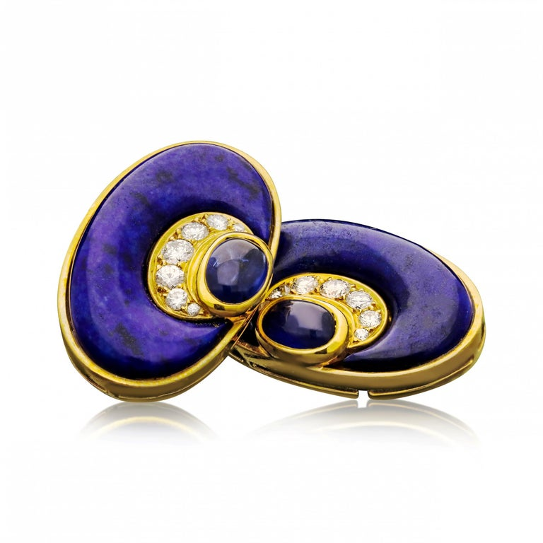 A wonderfully stylish and colourful pair of vintage earrings by Bulgari c.1970s, made in 20ct yellow gold and of large oval form, the earrings each set with a crescent moon shaped piece of carved and polished rich blue lapis lazuli, the inside curve