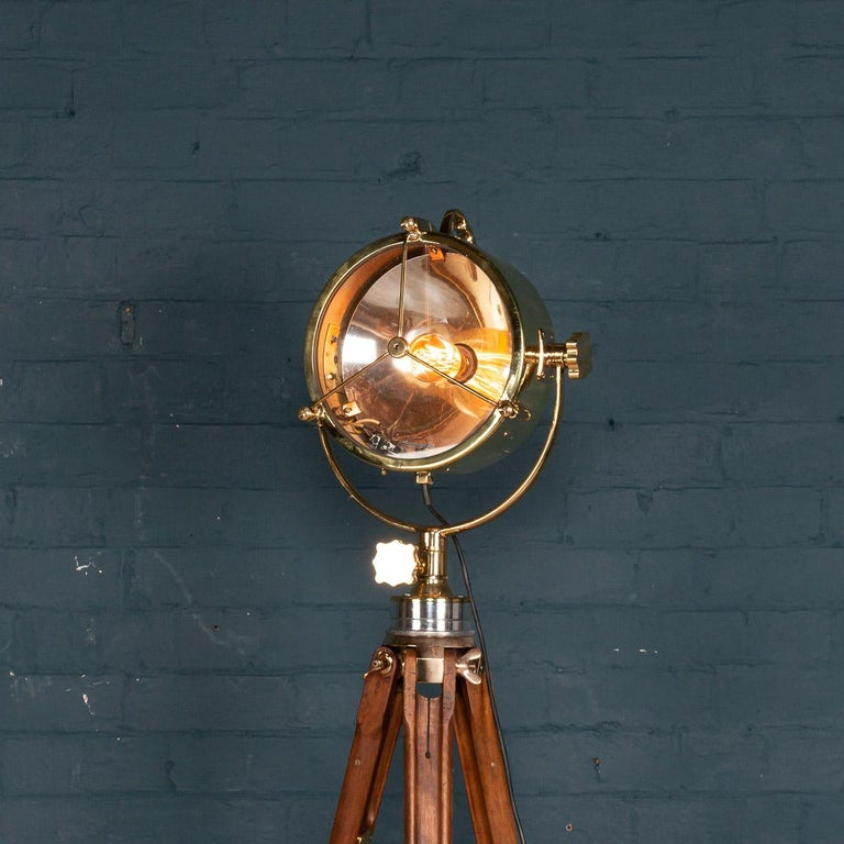 A fantastic mid-20th century English naval searchlight, mounted on an earlier 20th century tripod. These lamps would have been mounted on military or shipping vessels. With a contemporary squirrel cage light bulb, this example has been