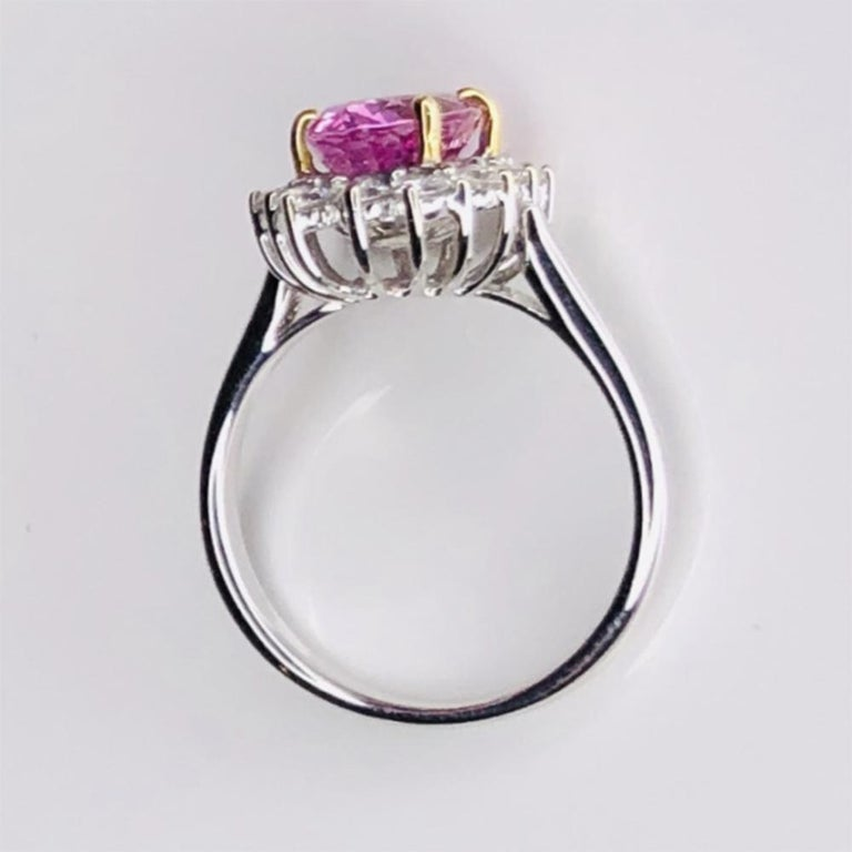 Simply Beautiful! Elegant and finely detailed Mid Century Modern Solitaire Cocktail Engagement Ring, set with a securely nestled 2.32 Carat oval Pink Sapphire surrounded by Brilliant-cut Diamonds, weighing approx. 0.61 total Carat weight.  Circa