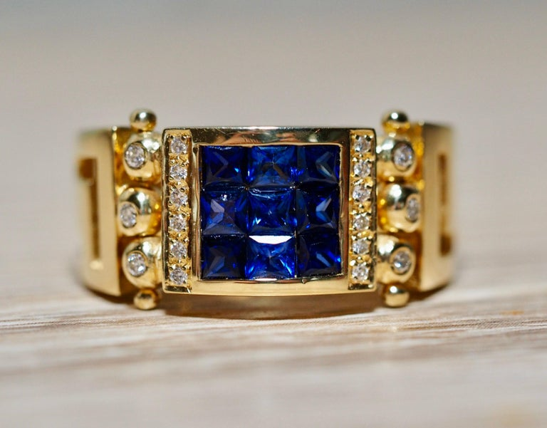 This incredible sapphire ring is detailed at every angle. The square center is made up of nine invisible set squared cut vibrant blue natural sapphires. The sapphires are framed in a yellow gold bezel with a row of diamonds on each side. Next to the