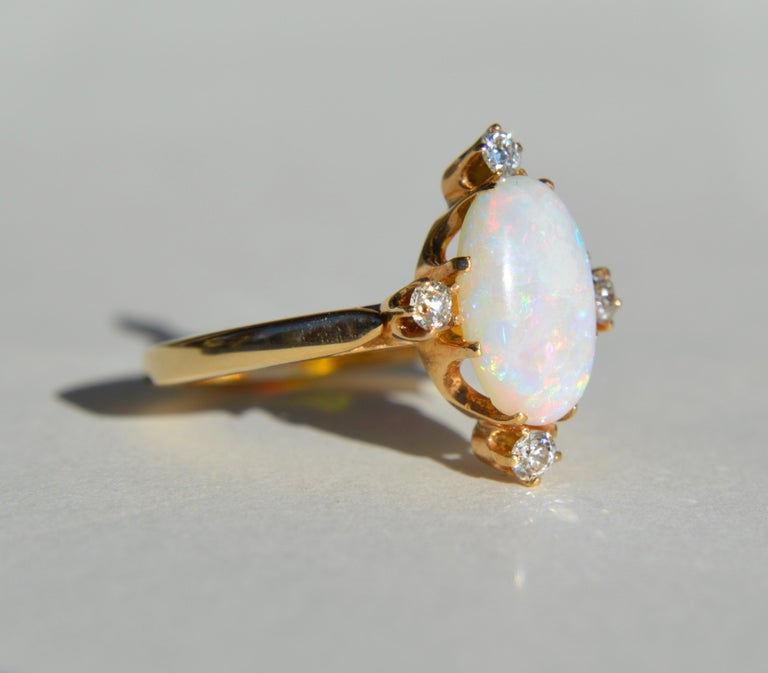Beautiful vintage circa 1980s 14K yellow gold featuring a 3 carat fiery rainbow flecked Australian opal cabochon with 4 round cut diamonds, each .11 carat (3mm diameter).  In very good condition. Ring is unmarked but acid tested as solid 14K gold.