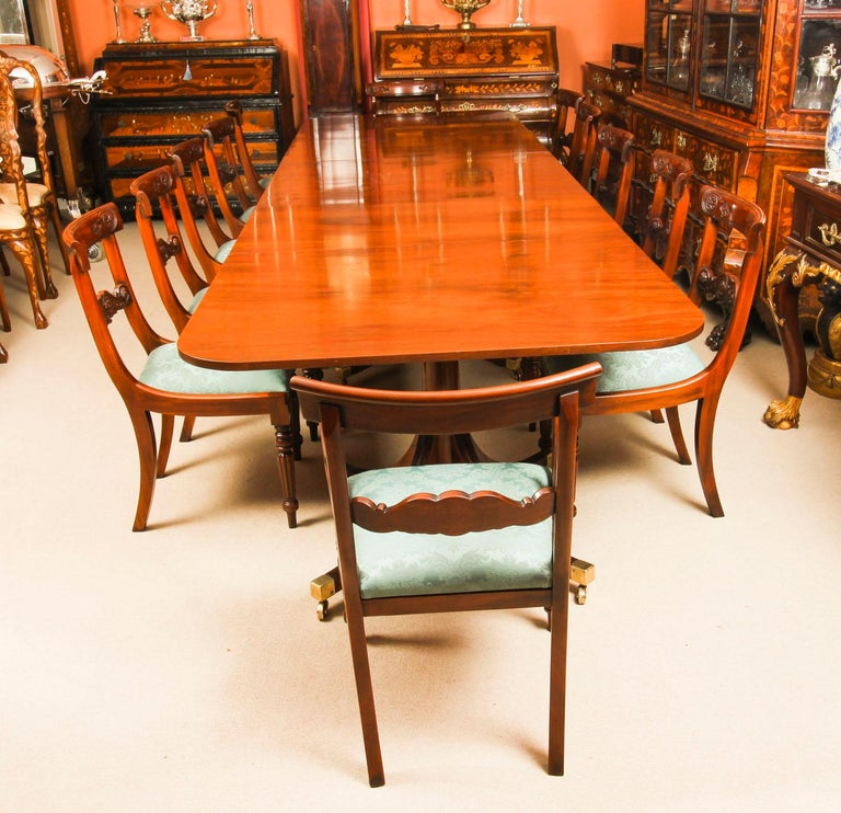 This is wonderful vintage dining set comprising a Regency style dining table by William Tillman and a set of twelve bar back dining chairs, circa 1980 in date.  The table is made of stunning solid flame mahogany and is raised on three