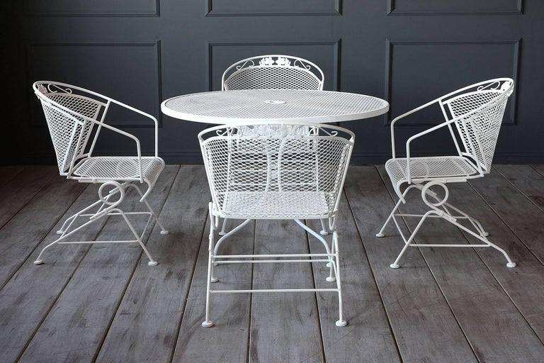 This 1960s five-piece outdoor dining set includes a dining table and four armchairs made of iron finished in an off-white color. The dining table features a classic design with a pedestal base and a mesh wire top with an umbrella stand in the
