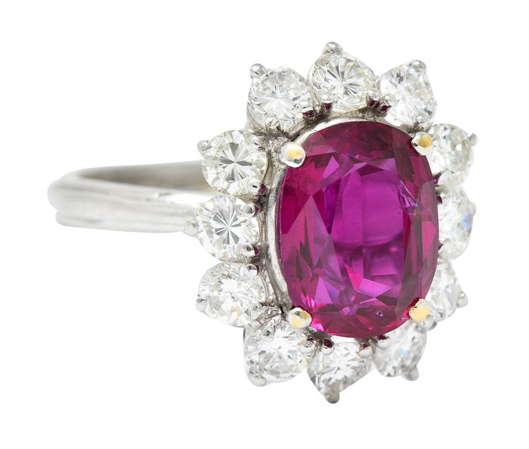Cluster ring centers an oval cut ruby weighing 3.77 carats  Transparent and very slightly purplish red in color with no indications of heat - Thai in origin  Surrounded by a halo of round brilliant cut diamonds  Weighing in total approximately 1.25
