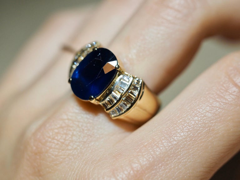 This elegant 18 karat yellow gold sapphire ring dates back to the 1970's. The center includes a 5.53 carat oval sapphire center. The deep blue color radiates as it touches the light. The sapphire is accented with a double row of invisible set