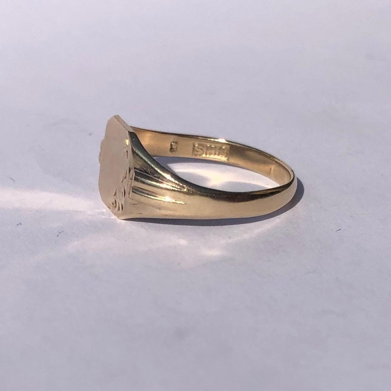 This sweet signet is modelled in 9ct gold and has a square face with half of it gently moulded with scroll detail. Made in London, England.   Ring Size: O or 7 Face Dimensions: 8.5x8.5mm   Weight: 2g