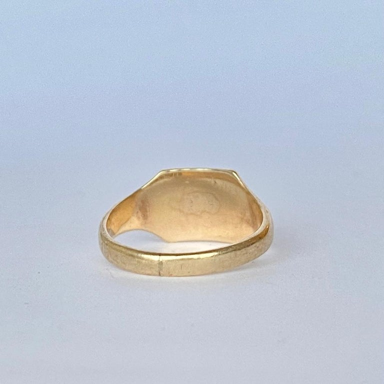 This sweet signet is modelled in 9ct gold and has a square face with half of it gently moulded with scroll detail. The initials engraved are 'E.M.K'. Fully hallmarked Birmingham 1961.  Ring Size: K 1/2 or 5 1/2  Face Dimensions: 8.5x9mm   Weight: