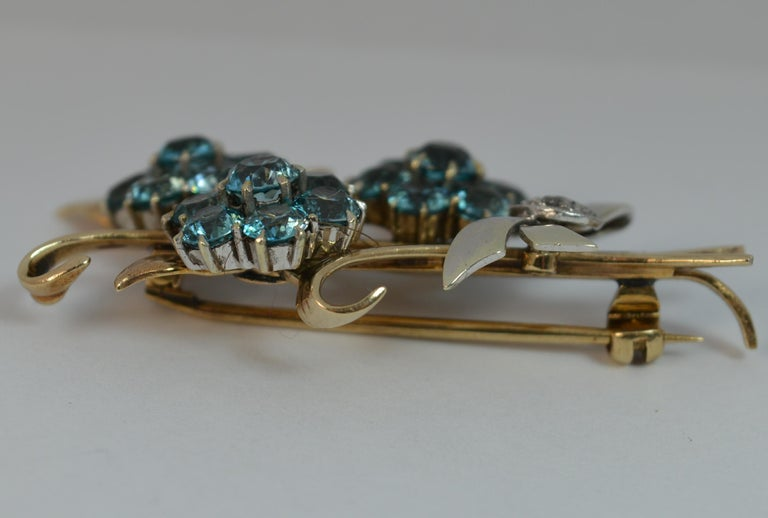A stunning true vintage brooch of floral spray design.  Solid 9 carat rose gold and platinum example.  Set with three clusters of round blue zircon stones forming flower heads with a bow ribbon to base set with little rose cut diamonds.   CONDITION