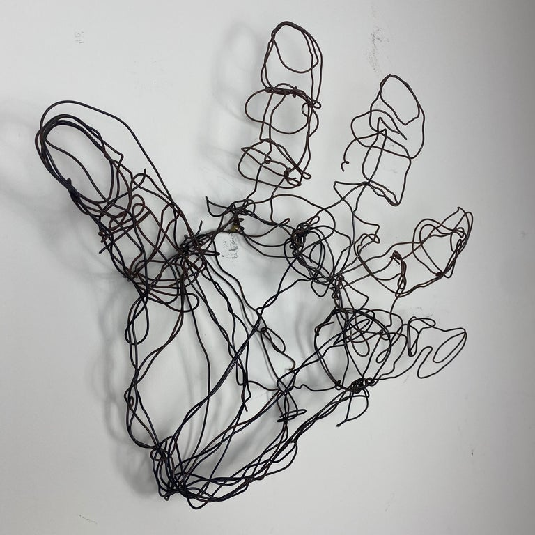Formed wire abstract wire hand sculpture. A light patina has formed on the steel wire giving this abstract sculpture and warm appearance. Can be wall-mounted or simply rest on a surface.