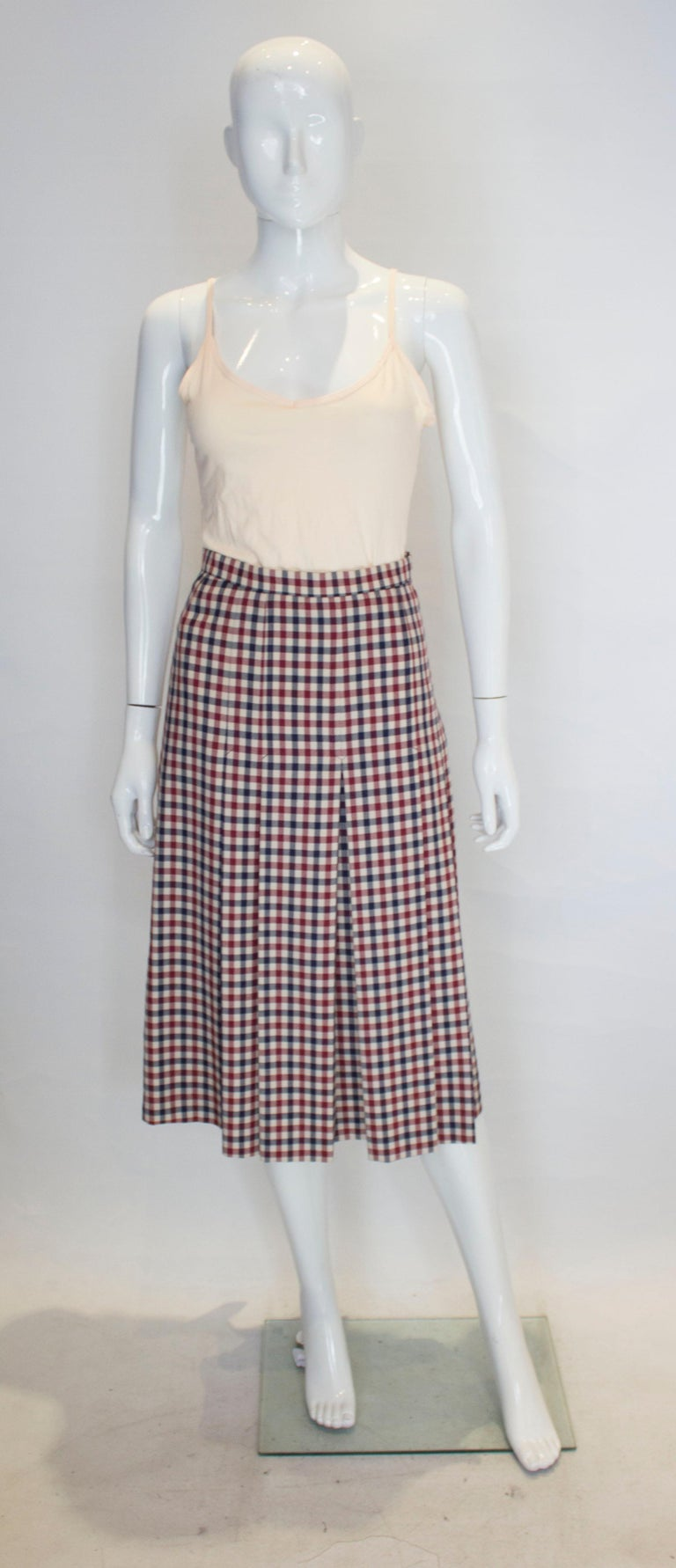 A great skirt for Fall, from British firm Acquasctutum. The skirt is in a burgundy, cream and blue check. It is knee length, fully lined with box pleats and a side zip.