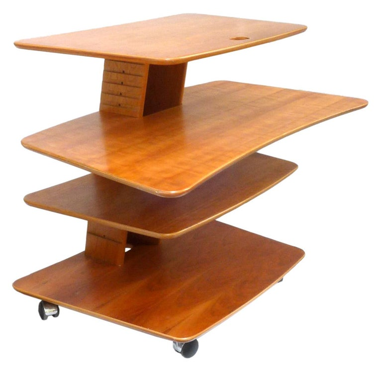 A fantastic, rolling, adjustable table or workstation by Aksel Kjersgaard for Levenger. Classic 1970s Danish modern design, a fun and creatively-conceived beech-plywood construction with variously adjustable middle shelves, floating on casters for
