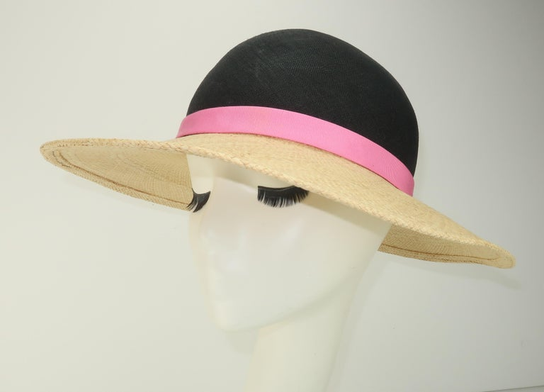 Simple and stylish!  An Adolfo II straw hat with natural brim, midnight blue (almost black) crown and a hot pink band for a little color splash.  Originally retailed at Saks Fifth Avenue ... previously owned though never worn with tag still