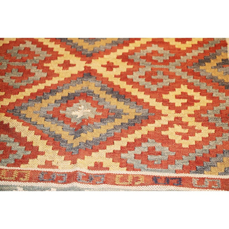 An exceptional 20th century Afghan Kelim, Afghan village, wool on wool foundation. A colorful design with polychrome field with three conjoined stepped and hooked radiating medallions within a red continuous hooked and stepped medallion border. The