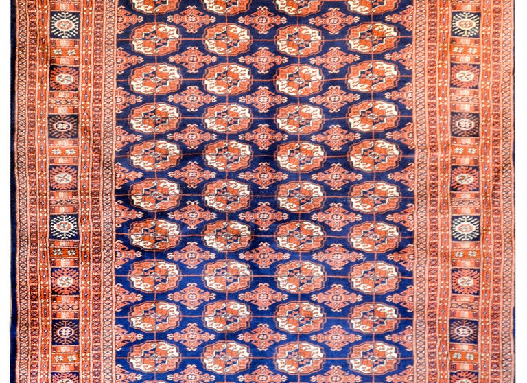An exceptional vintage Afghani Bokhara rug with an all-over stylized floral medallion pattern woven in white, indigo, and orange vegetable dyed wool, on a dark indigo ground. The border is extra wide, comprised of multiple petite and wide stylized