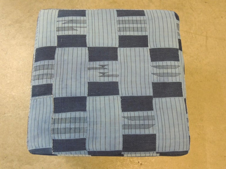 Vintage African blue and indigo woven textile custom square ottoman. Wood frame with padded construction all around and small tack feet. The Yoruba are masters of the indigo-dyeing process. They also have the most varied methods of applying resists