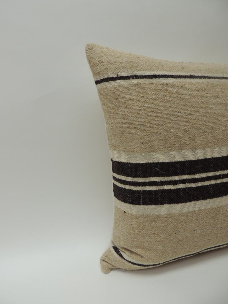 Vintage African woven tribal artisanal textile decorative pillow. Tunisian vintage artisanal tribal textile decorative pillows handcrafted from the vintage wool and hemp hand-loomed by the Berber tribes from the Atlas Mountains of Morocco. Natural