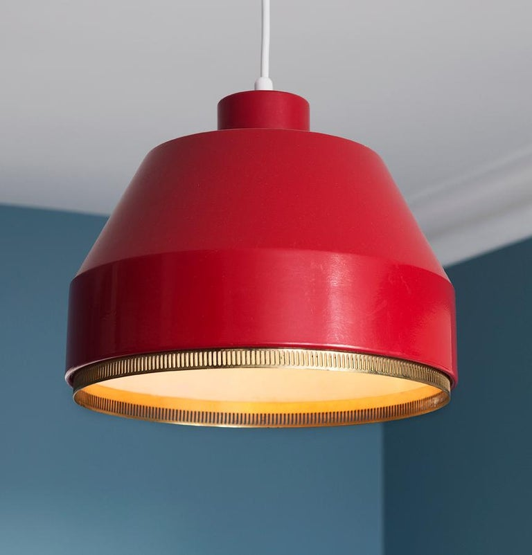Aino Aalto Finland, 1941  Red painted metal ceiling light with perforated brass ring.  About  Finnish architect Aino Aalto (1894-1949) graduated from Helsinki Polytechnic in 1920. She joined Finnish architect Alvar Aalto's studio in 1924 and