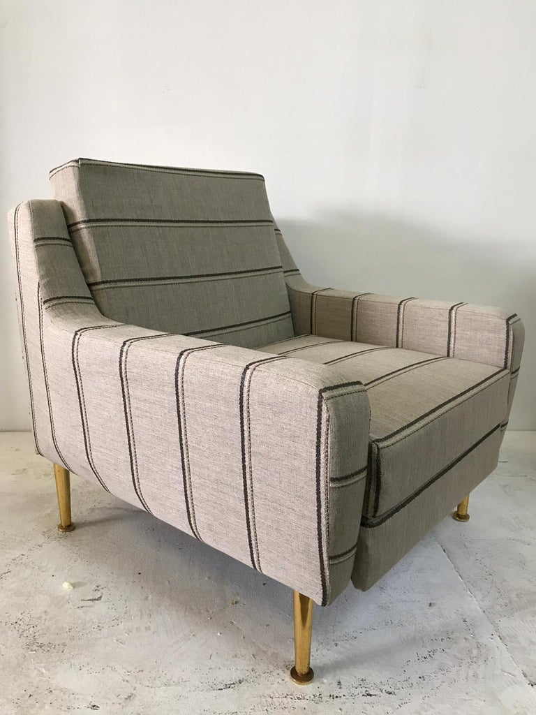 This is a wonderful 1950s Classic Italian designer chair, reupholstered in a natural linen. Original brass feet and headrest. The headrest can be hidden, will make the height of chair 34 inches tall when up.