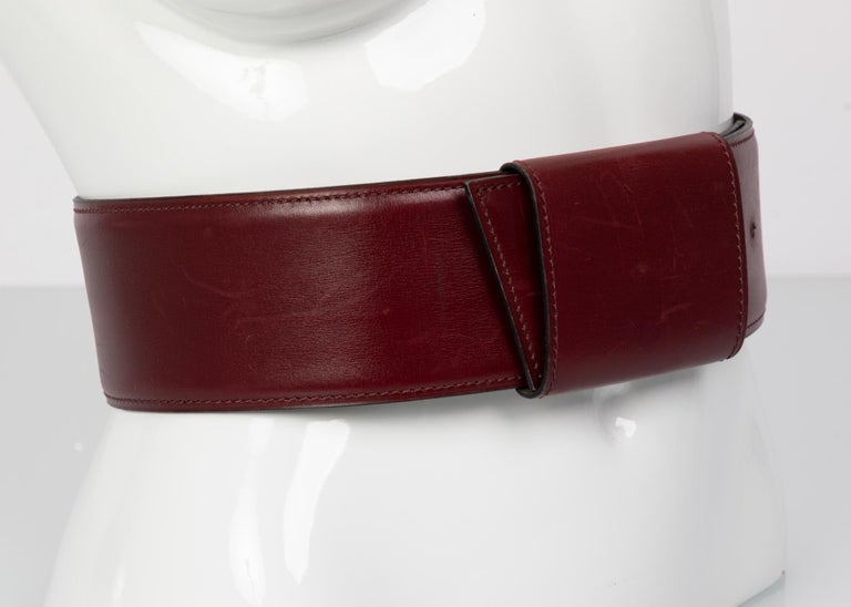 Bordeaux leather Alaïa waist belt with tonal stitching and peg-in-hole pull-through closure. In very good condition, with minor wear to leather.  Measurements: Length Min: 26 inches Length Max: 28 inches Width: 2.75 inches