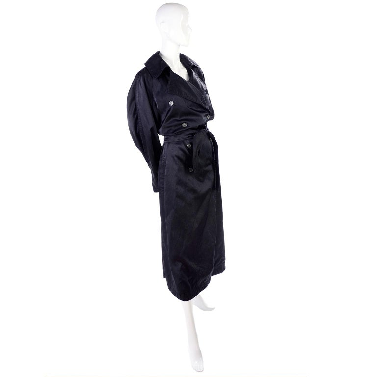 This is a great vintage Alaia long trench coat style raincoat with waist belt. This double breasted designer rain jacket has side slit pockets and can be worn buttoned all the way up, or with the lapels out. It has a pleated slit running up the back