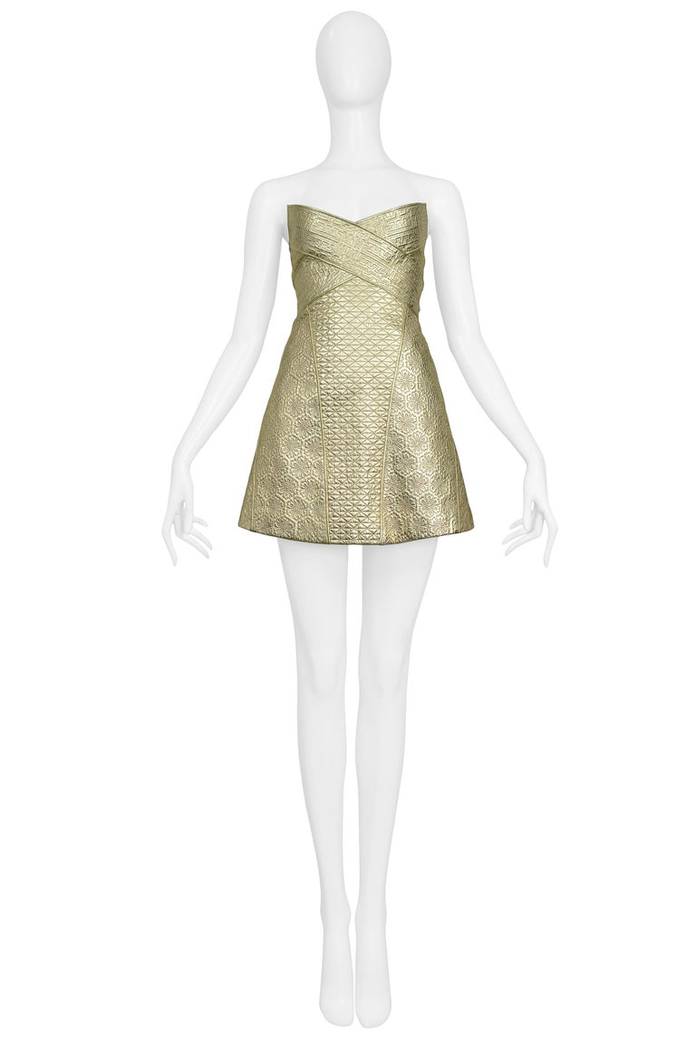 Resurrection is excited to offer a vintage Alexander McQueen gold leather armor dress featuring contrasting quilted and embossed designs, a strapless v front, a-line skirt, and center back zipper.   Alexander McQueen  Size 42 100% Leather - 100%