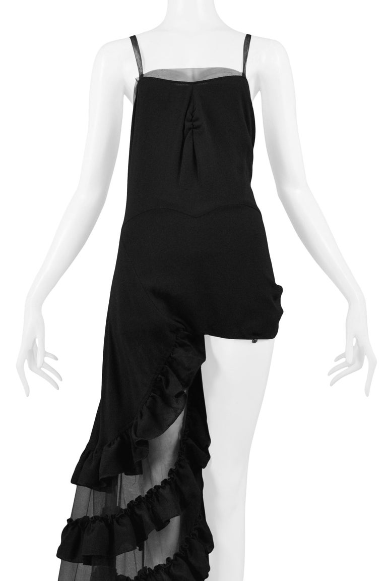 We are excited to offer this iconic black Alexander McQueen one-legged evening gown from the SS 'NO. 13', 1999 runway collection. The gown's wrap skirt can be buttoned to expose one leg or buttoned to create a full skirt (both legs covered). Shown