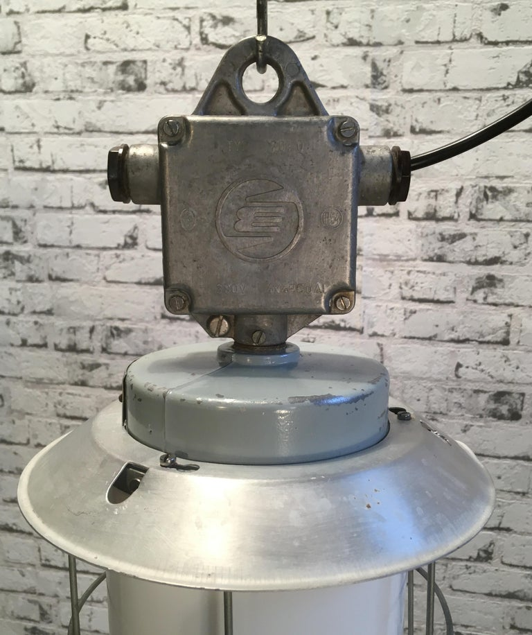 This industrial lamp in aluminium with milky glass was produced during the 1970s. In former Czechoslovakia by Elektrosvit. Iron cage. New socket E 27 and wire. Weight of the lamp is 2 kg.