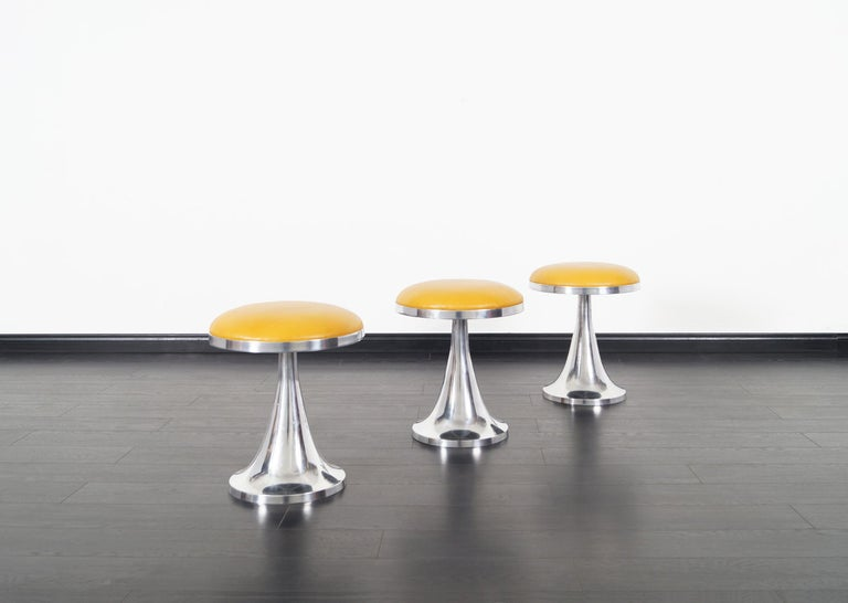 Set of three vintage aluminum stools. Newly reupholstered in this gorgeous butterscotch leather.