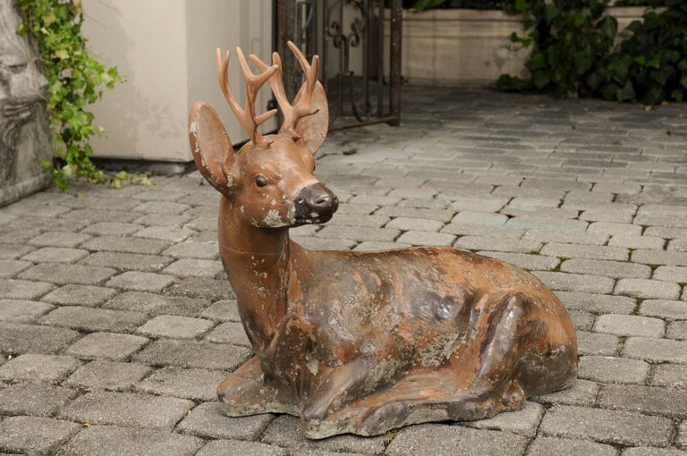 A vintage American concrete deer sculpture with iron antlers and weathered patina. Born during the first half of the 20th century, this deer sculpture charms our eyes with its touching representation. Boasting a nicely worn appearance, the sculpture