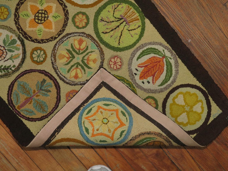 An American hooked rug dated 1980 with a colorful multiple circular design featuring different fruits, animals and plants.