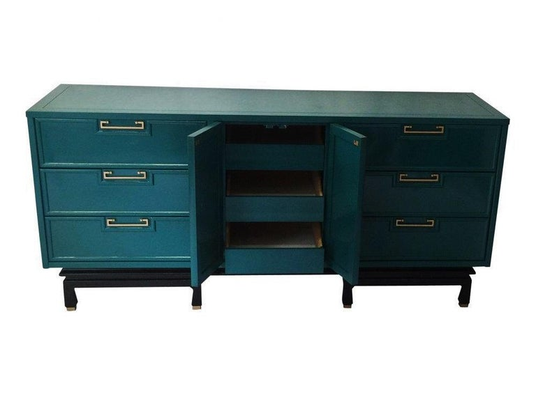 Gorgeous vintage modern American of Martinsville dresser / credenza lacquered in teal with a black base. There are nine double dovetail drawers-three of which are behind the doors in the center. The original hardware has been polished along with the