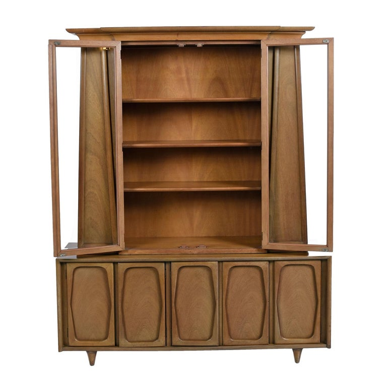 Our crew is enamoured by the unique design of this two-piece china hutch. We give respect to the heavy duty, over engineered American craftsmanship. The style is an interesting mix of Mid-Century Modern and Art Deco design. The pyramid shaped top