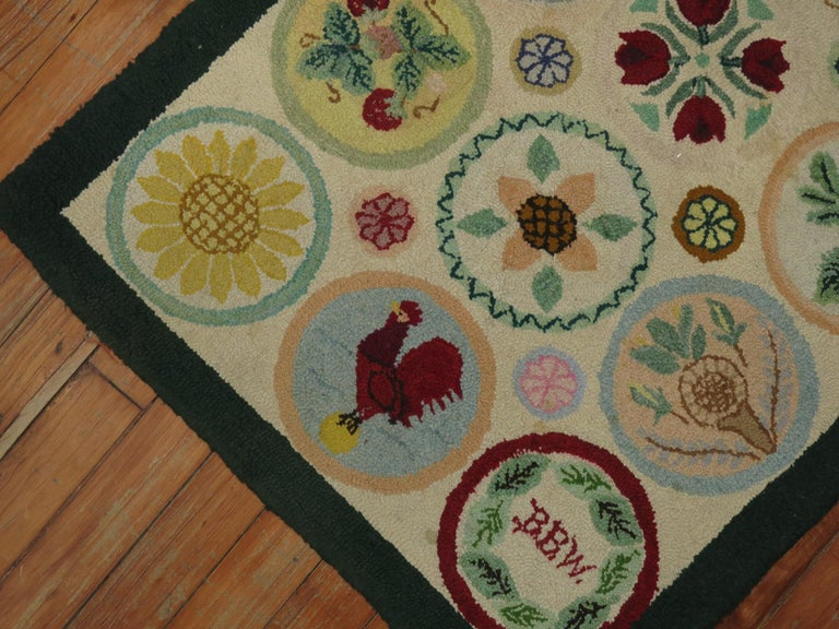 American hooked rug from the late 20th century. An array of fruits and on circular medallions. A rooster spotted on one of the medallions. Initials of weaver found on another medallion.