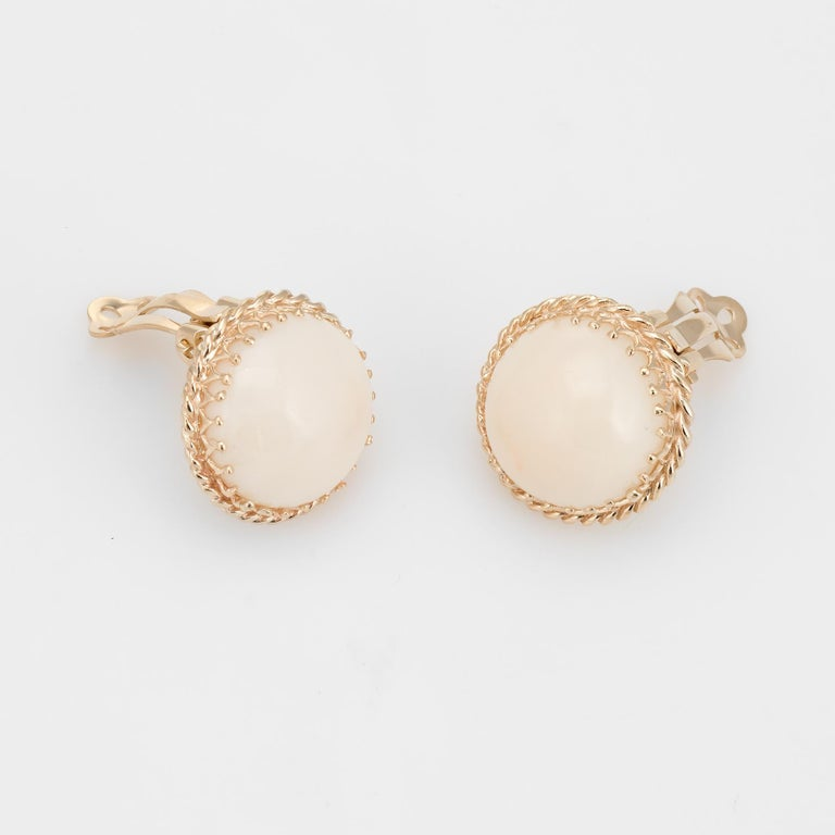 Finely detailed pair of vintage angel skin coral clip earrings (circa 1950s to 1960s), crafted in 14k yellow gold.   Cabochon cut angel skin coral measures 15mm each - 9 carats each (18 carats total estimated weight). The coral is in excellent
