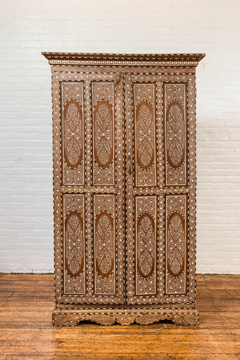A vintage Anglo-Indian inlaid wooden wardrobe cabinet from the mid-20th century, with ebonized accents, bone and horn inlay. Capturing our attention with its intricate decor, his tall cabinet is adorned with an abundant décor of foliage and