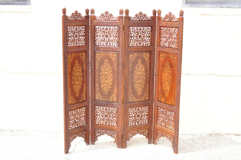 Vintage Anglo-Indian teak wood brass inlay 4 panel room divider folding screen. Item features ornate brass inlay, 4 folding panels, nicely carved details, very nice vintage item, great style and form. Circa mid to late 20th century. Measurements: