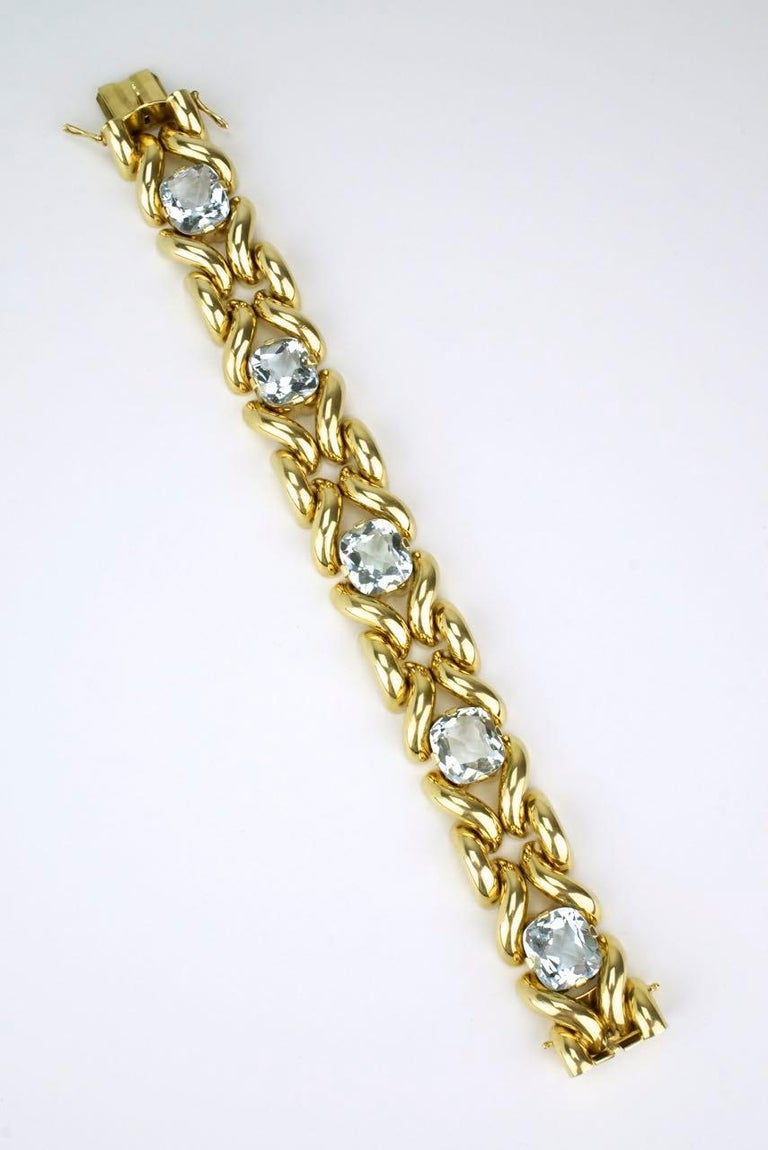 An aquamarine and 14k yellow gold fancy link bracelet with five pale blue cushion cut aquamarine stones of very good clarity claw set in a knot link motif bracelet with a box clasp and two figure of eight safety clasp closures.  This Luxe bracelet
